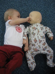 Baby with a resuscitation doll