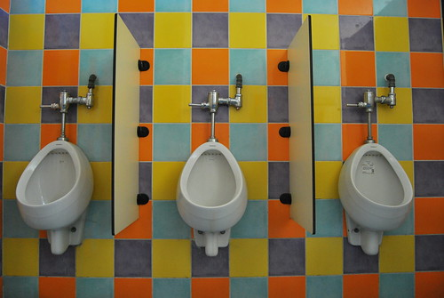 3 urinals and a colorful wall