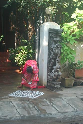 Ein Hausmädchen streut ein Kolam Muster vor einem Haus in Pondicherry