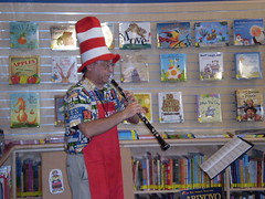 Librarian Ed Koetitz wearing a Cat in the Hat hat and playing an oboe in the children's area of the library