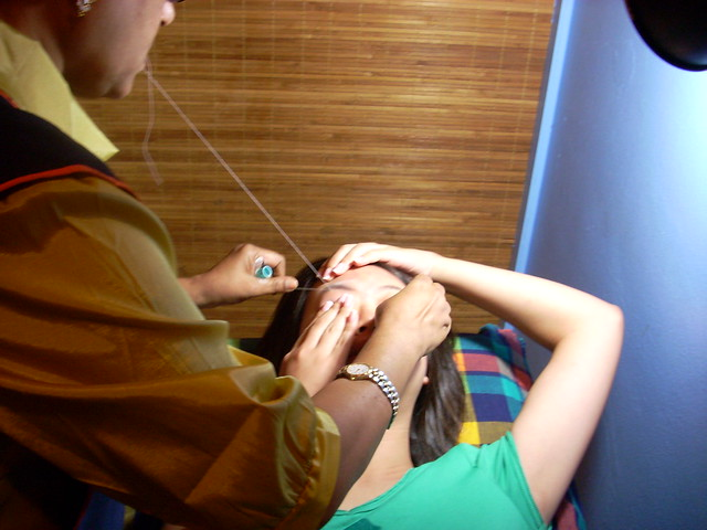 threading her eyebrows.
