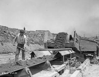 Worker loading dirt on conveyor belt during second Denny Regrade, 1930