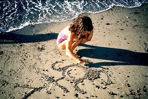 my daughter drawing in the sand at the beach