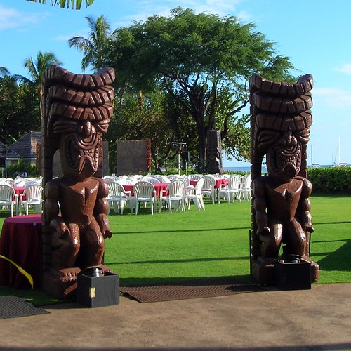 A pair of tikis ready to greet guests at an evening luau.