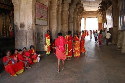 Eine Gruppe von Frauen in roten Saris wartet in einem Durchgang von Sri Rangam