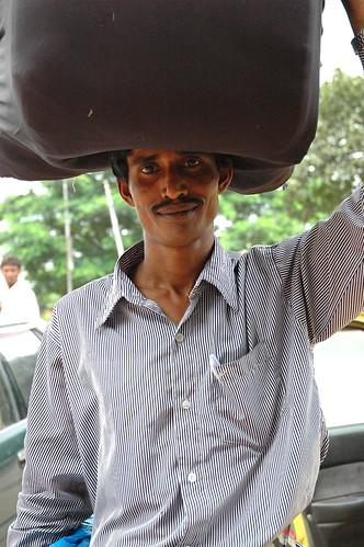 Man carrying a load, Jatiyo Smriti Soudho Independence memorial park and gardens parking lot, Savar, Dhania, Dhaka, Bangladesh by Wonderlane