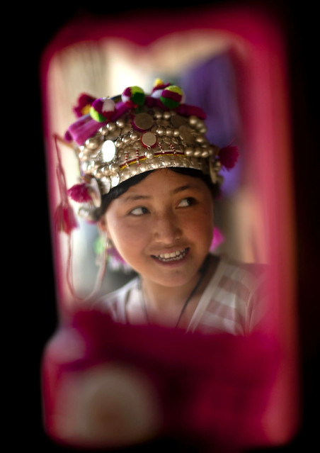 Young Akha girl preparing herself in front of a miror before going to see ...