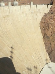 Hoover dam river side showing vast wall with road across top and power generating station below