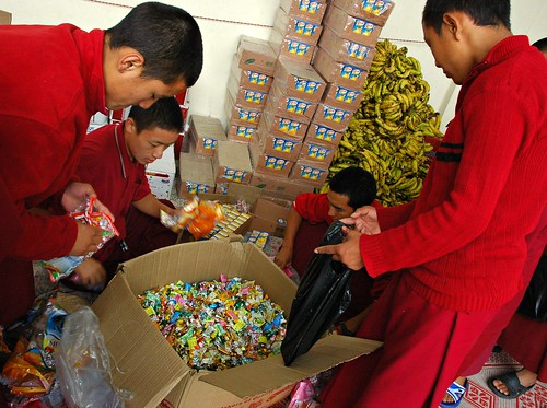 Big box of candy for the celebration manga, with several young monks readying the feast, Tharlam Courtyard Stage, Boudha, Kathmandu, Nepal by Wonderlane