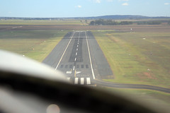airline(0.0), wing(0.0), aerial photography(0.0), landing(0.0), takeoff(0.0), field(1.0), plain(1.0), infrastructure(1.0), tarmac(1.0), runway(1.0),