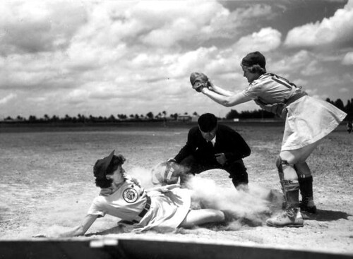 All American Girls Professional Baseball League player Marg Callaghan sliding into home plate as umpire Norris Ward watches: Opa-locka, Florida