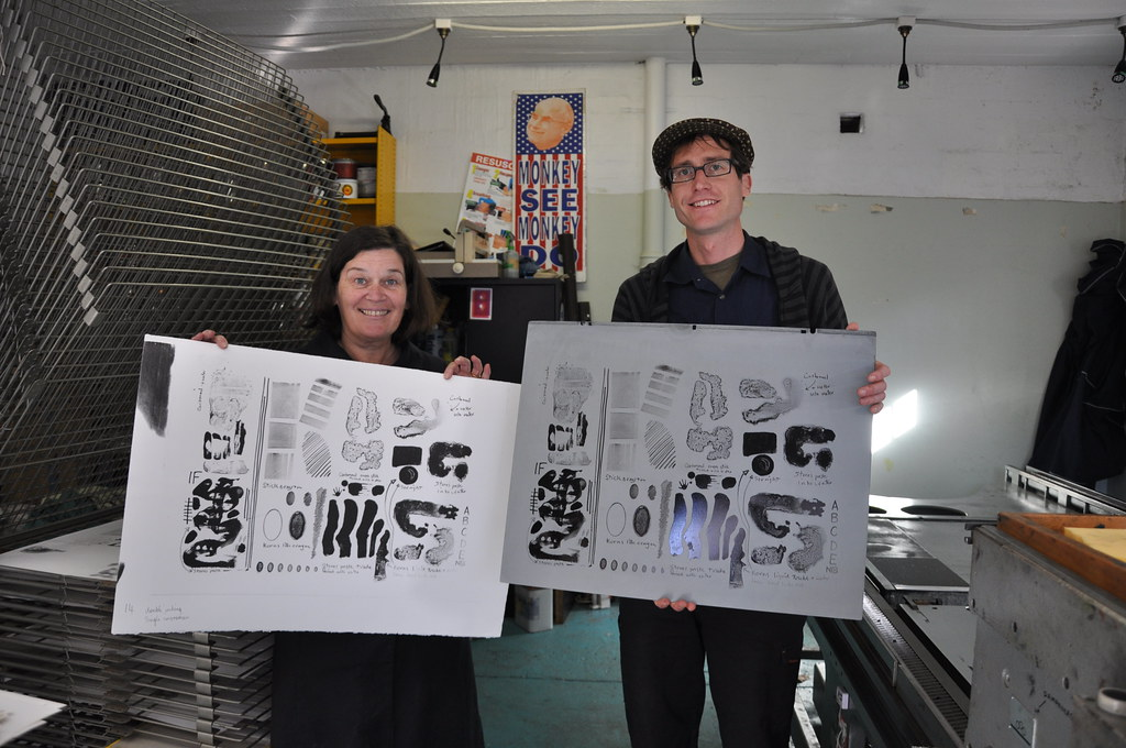 the happy printer shows off the plate while the happy artist shows off the print