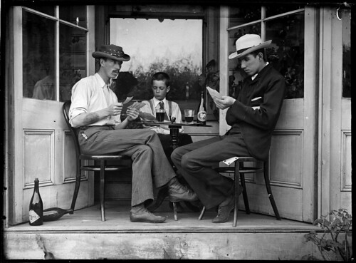 Three men playing cards in an alcove