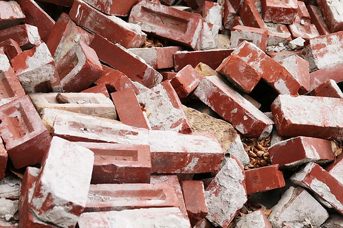 a large pile of red bricks, some with dried mortar still attached