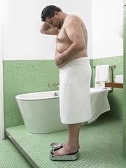 man_met_overgewicht_op_weegschaal