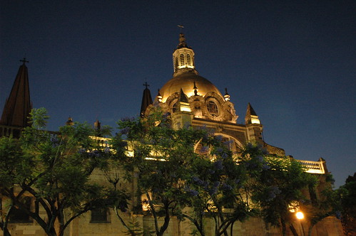 Cathedral lit at night on Tsok Kor, with purple flowering trees, Guadalajara public square, Jalisco, Mexico by Wonderlane