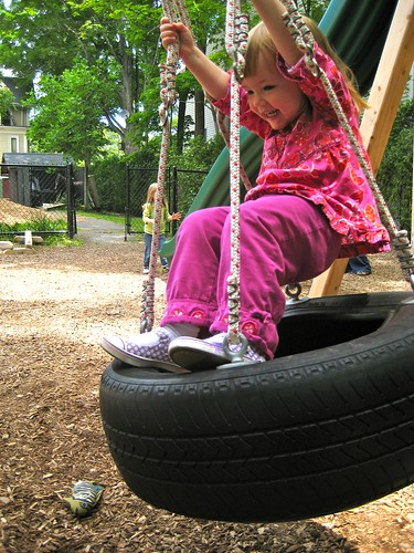 girl riding tire swing