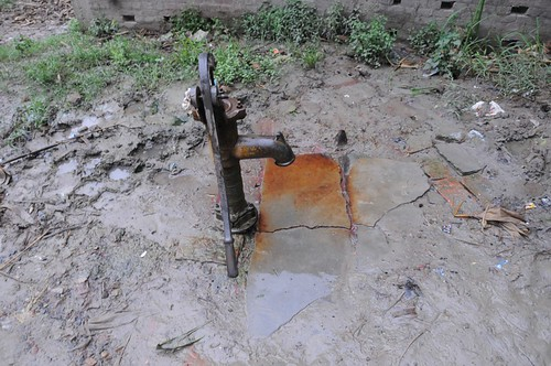 A traditional handpump or Chapakal with red stains at the base