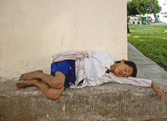 Street boy sleeping. 2 views