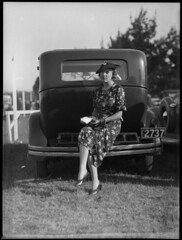 Woman sitting on bumper bar of a car at Warwick Farm racecourse