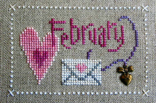 Cross stitch of February in pink thread on grey background with hearts and an envelope