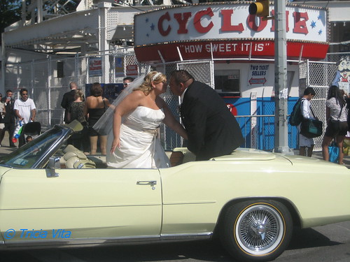 Bride & groom kiss in front of Cyclone roller coaster