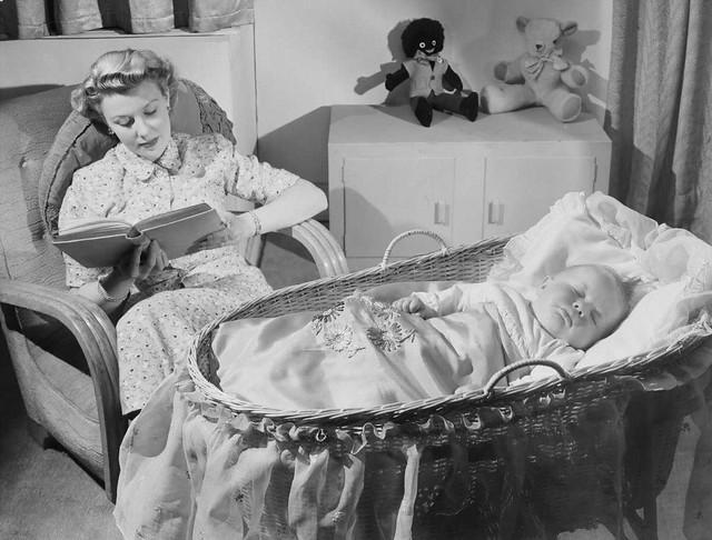 Woman reads as baby sleeps