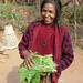 Woman in Nepal showing leafy vegetables from home garden by farmingmatters