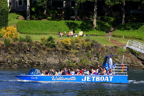 willamette jetboat cruising past a family in their riverfront back yard