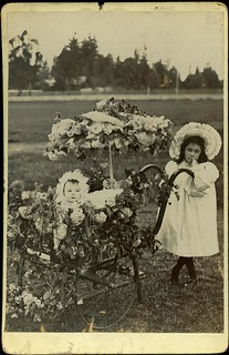 Outdoor portrait photograph of a young girl with a baby in a pram and parasol, both bedecked with flowers. Probably from a Whit walk or a carnival, 1900-10.