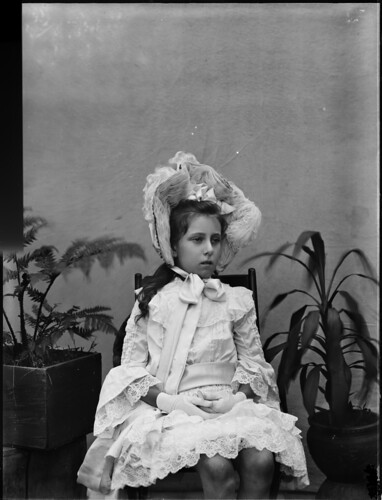 Portrait of young, bare legged girl, seated on wooden chair