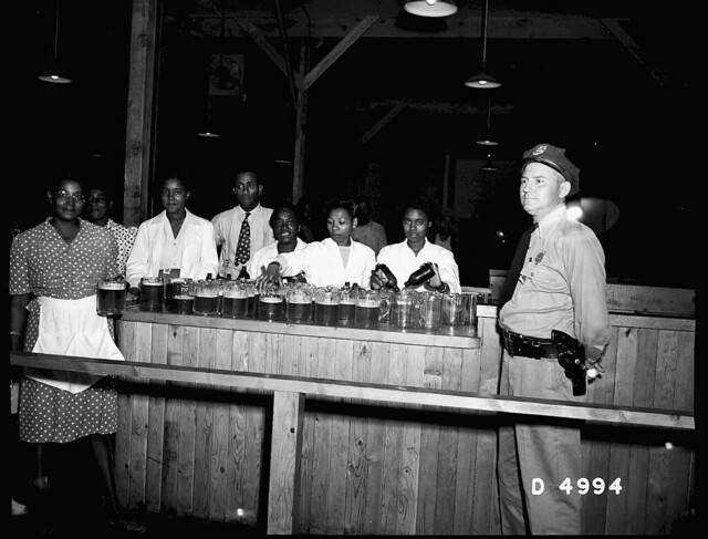 WAITRESSES PREPARING SERVING PITCHERS - SECURITY GUARD STANDING CLOSE BY