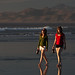 Two attractive young ladies feeling good and walking on the wet sand holding what looks to be giant-sized Dos Equis beer bottles - drinking beer on the beach at sunset