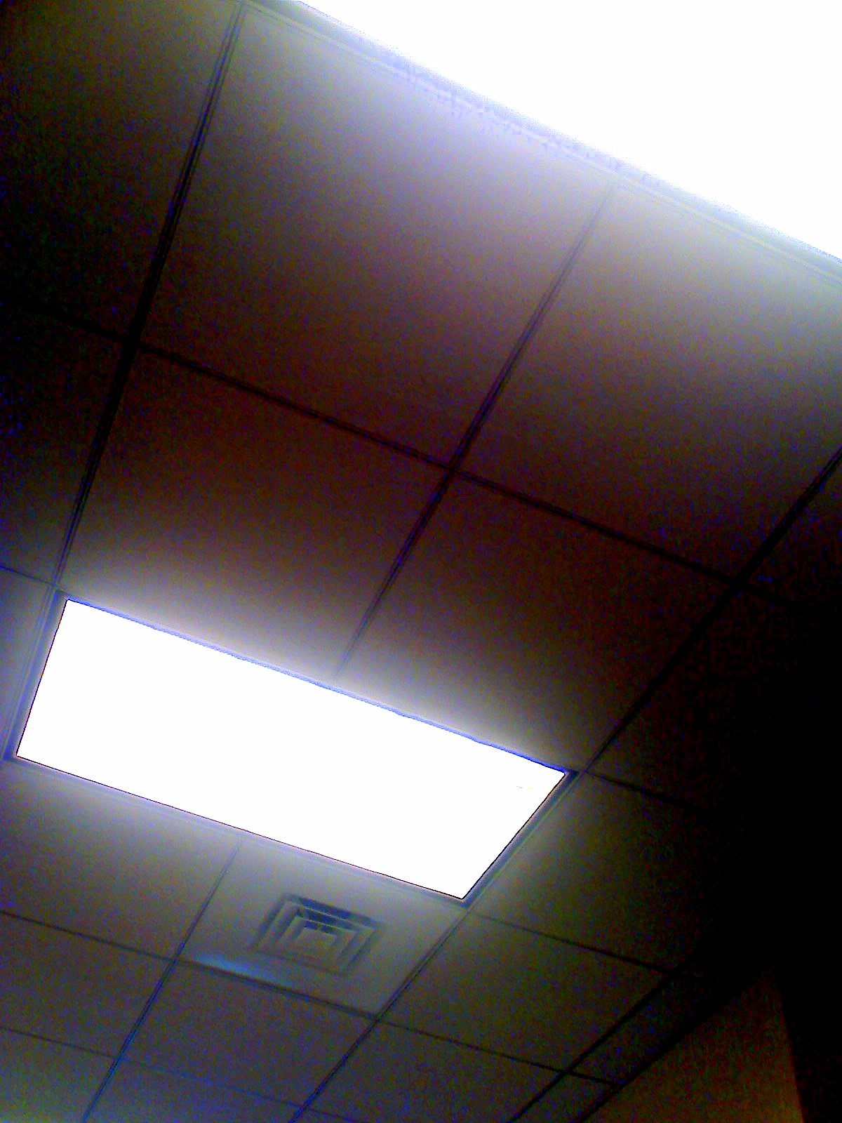 Fluorescent light panels on the ceiling of an office hallway