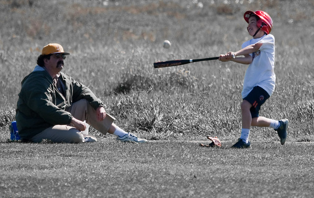 Father and son baseball batting lesson in the Cloisters Park, Morro Bay, CA