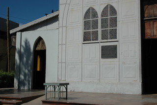 Metal church designed by Gustave Eiffel, left side entrance and gothic shaped metal bench, San Rosalia, Baja California Sur, Mexico