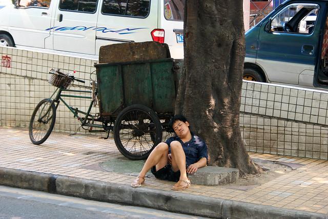 A tired cyclist in Guangzhou, China.