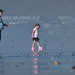 A mother and daughter walk on the wet sand reflecting their images at low tide