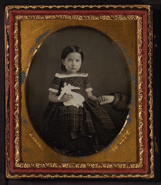 Girl with doll, holding mother's hand