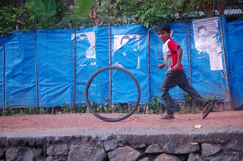 Ein Junge läuft mit einem einzelnen Fahrrad vor blauem Gartenzaun