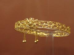 brooch(0.0), lighting(0.0), yellow(1.0), metal(1.0), jewellery(1.0), bangle(1.0), headpiece(1.0), gold(1.0),