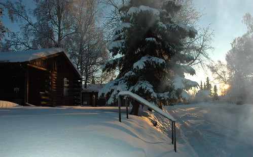 One of the few log cabins in Anchorage, Alaska, USA, in the snow and sun, with a little fog, Christmas
