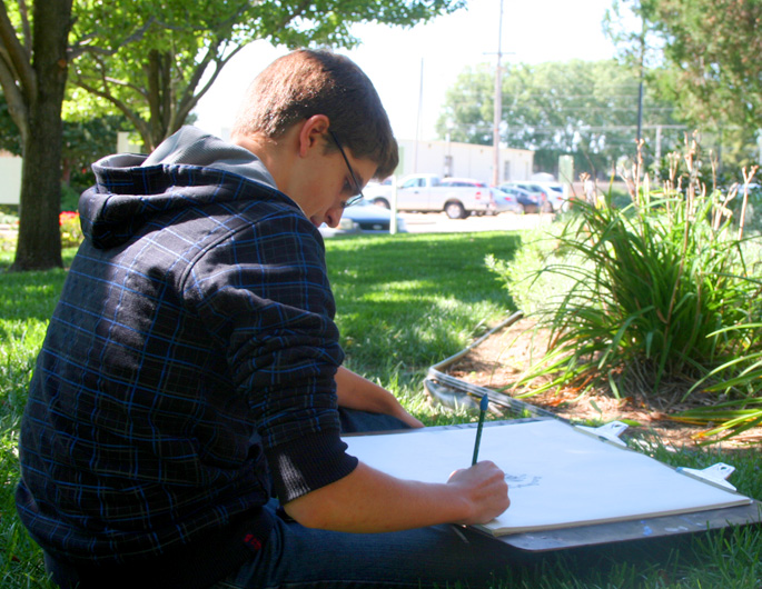 Newman art student in class outside