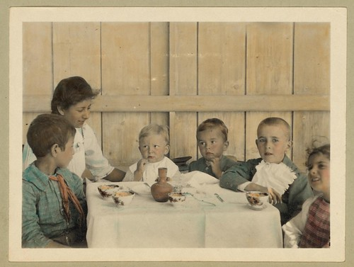 Vintage Picture of Children Sitting Down at a Table about to Eat a Meal, Boys, Girl, Woman