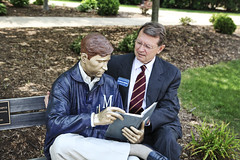 Millikin's president, Dr. Jeffcoat, enjoys a book with Mr. Bronze Man!