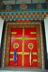 "Red door, with brass handles and symbolic ""tah-sing"" silk cloth pulls, Tharlam Monastery, Boudha, Kathmandu, Nepal"