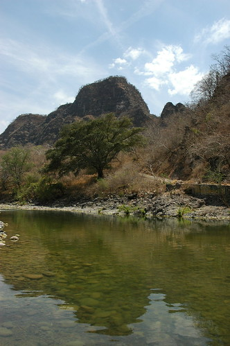 Hot sunny day at the swimming hole, round rocks under the still green waters, tree and hill, by the side of the road, San Cristobal de la Barranca, Jalisco, Mexico by Wonderlane