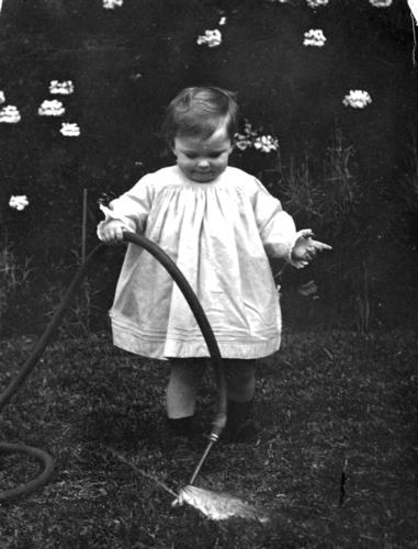 Toddler playing with a hose in a garden