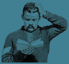 Man scratching his head while reading a book