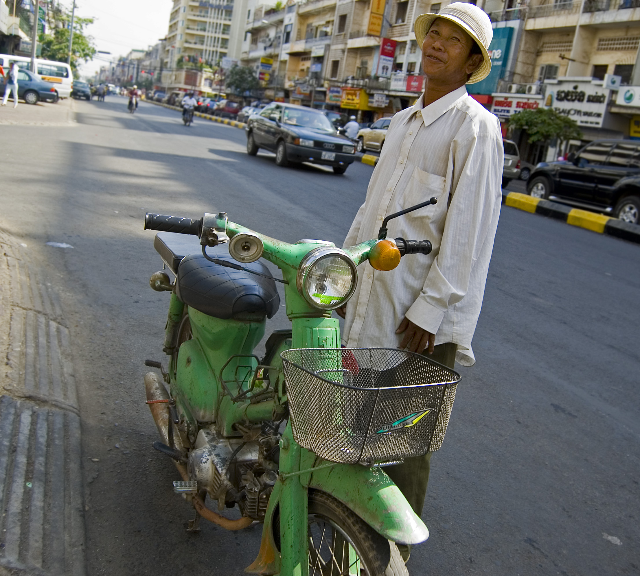 Moto taxi driver in front of some apartments in Phnom Penh, Cambodia